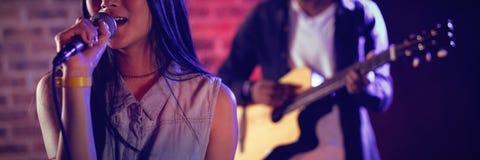 唱歌由吉他弹奏者的妇女在俱乐部 库存图片