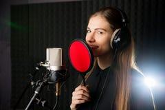 唱歌的女孩在录音室 免版税库存照片