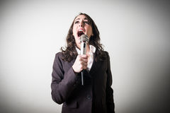 唱歌的美丽的年轻女实业家 免版税库存图片