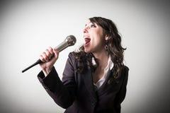 唱歌的美丽的年轻女实业家 库存图片