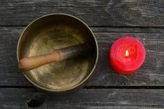 唱歌碗和燃烧红色蜡烛 免版税库存照片