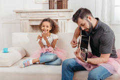 唱歌非裔美国人的女孩,当在家时弹吉他的父亲 免版税库存照片