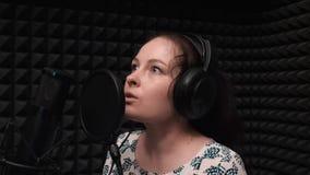 唱浪漫歌曲的年轻可爱的妇女对专业话筒 排练歌曲的唱歌的女孩 股票录像