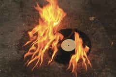 唱片烧在沥青的明亮的橙色火焰 免版税库存照片