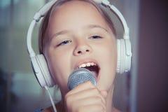 唱白种人儿童女孩特写镜头  女孩情感地唱歌入话筒,举行它用手 免版税库存图片