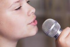 唱白种人儿童女孩特写镜头  女孩情感地唱歌入话筒,举行它用手 库存图片