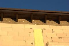 啄木鸟损伤和孔对房檐在屋顶下 免版税库存照片