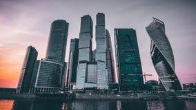 商业中心有现代未来派摩天大楼大厦的莫斯科市在河反射了在夏天晚上在日落时间 图库摄影