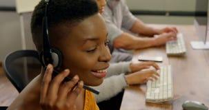 商业主管与在书桌4k上的耳机一起使用 股票录像