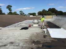 商业屋顶平台泄漏修理;盖屋顶的人, 免版税库存图片
