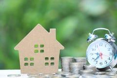商业投资和不动产、堆硬币金钱和自然绿色背景的,挽救式样房子为准备  库存照片