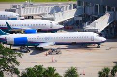 商业班机飞机被连接到终端 库存照片