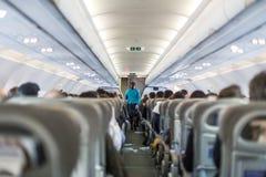 商业飞机内部有空中小姐服务乘客的在飞行期间的位子的 免版税库存图片