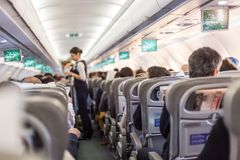 商业飞机内部有空中小姐服务乘客的在飞行期间的位子的 库存照片
