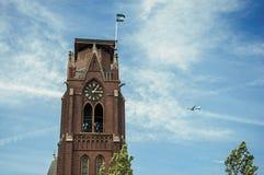 商业飞机飞行特写镜头在晴朗的蓝天和砖尖顶的在韦斯普 免版税库存照片