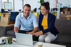 商业主管谈论在膝上型计算机 库存照片
