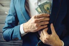 商人、成员或者官员在他的口袋投入贿款 免版税图库摄影