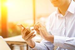 商人、智能手机、膝上型计算机和日落 免版税库存照片