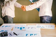 商人一起创造一个互利营业关系 在桌上的经济图表 库存照片
