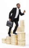 商人上升的硬币堆 免版税库存照片