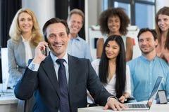 商人上司谈话在混合种族站立后边在现代办公室的商人小组的手机电话 库存照片