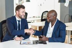 黑商人与一白种人一个握手在办公室 库存照片