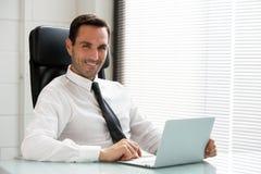 商人与便携式计算机一起使用 库存图片
