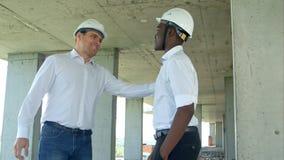 商人与在建造场所的建造者握手 免版税库存图片
