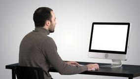 商人与在梯度背景的一台计算机一起使用 股票视频