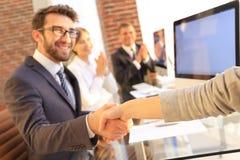 商人与坐在您的桌面附近的商务伙伴握手 库存图片