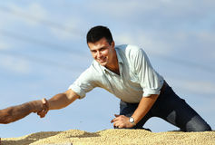 商人与大豆堆的工作者握手 免版税库存照片