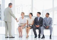 商人与妇女握手由人等待的采访 免版税库存照片