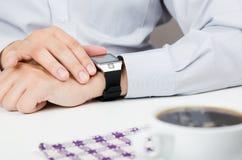 商人与巧妙的手表一起使用在餐馆 图库摄影