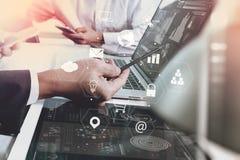 商人与巧妙的电话和便携式计算机一起使用在木头 免版税库存照片