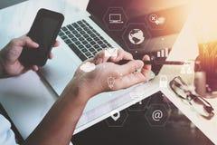 商人与巧妙的电话和便携式计算机一起使用在木头 免版税库存图片