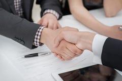 年轻商人与彼此握手在事务 免版税库存图片
