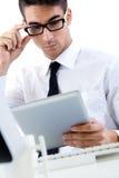 年轻商人与数字式片剂一起使用在现代办公室 库存图片