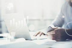 商人与普通设计笔记本一起使用 在手上拿着智能手机 全世界连接技术接口 图库摄影