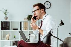 商人与智能手机和膝上型计算机一起使用,当吃午餐的时外卖面条 免版税库存照片