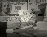 商人与膝上型计算机一起使用为赢得usd美元mone 免版税库存图片