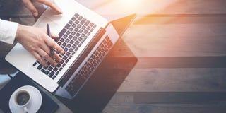 商人与膝上型计算机一起使用在办公室 现代笔记本,杯子在木桌上的无奶咖啡 在玻璃的反射 免版税库存照片