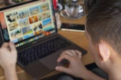 商人与膝上型计算机一起使用在城市咖啡馆 背景中断咖啡新月形面包杯子甜点 库存照片