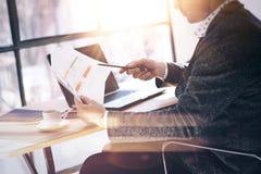 商人与膝上型计算机一起使用在晴朗的办公室 人分析举行在手上的文件 水平,视觉效果 库存图片