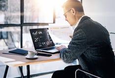 商人与膝上型计算机一起使用在晴朗的办公室 现代笔记本、在木桌上的杯子无奶咖啡和智能手机 免版税库存照片