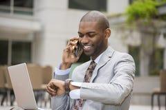 商人与膝上型计算机一起使用谈话在手机 免版税库存照片