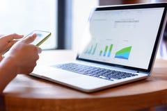 商人与膝上型计算机和智能手机一起使用 免版税图库摄影