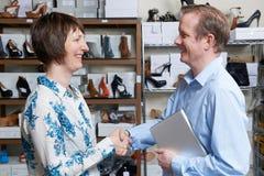 商人与鞋店零售商握手 库存照片