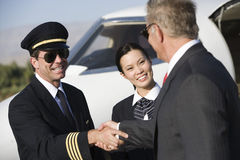 商人与飞机上尉握手 库存照片