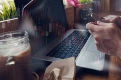 商人与他的在咖啡店的计算机一起使用与sto 库存图片