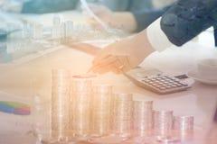 商人两次曝光与都市风景、硬币和图表的 免版税库存图片